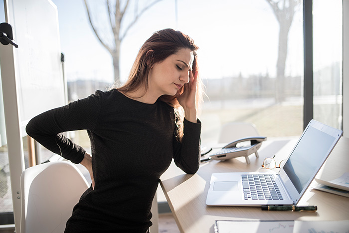 woman experiencing back pain in the office
